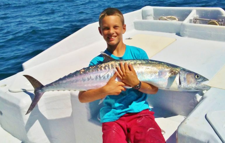 Boy holding fish on fishing charter at Anna Maria Island