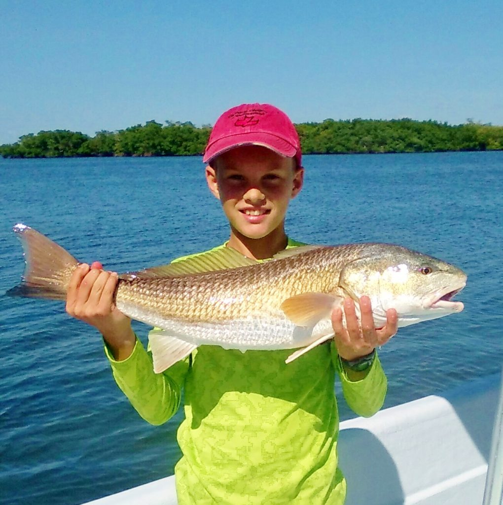 Boy on fishing charter on Anna Maria Island with fish