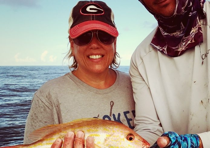 Man and woman holding large fish from deep sea fishing
