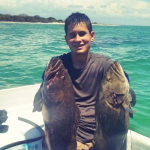 Boy holding two fish on Holmes Beach Fishing Charter