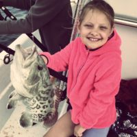 Girl smiling sitting beside caught grouper on Anna Maria Island fishing charter
