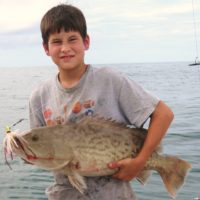 Boy holding fish two-handed on Anna Maria Island fishing charter