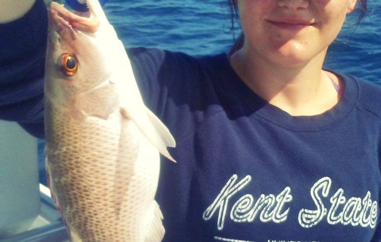 Young lady holding up fish at Anna Maria Island on a fishing charter