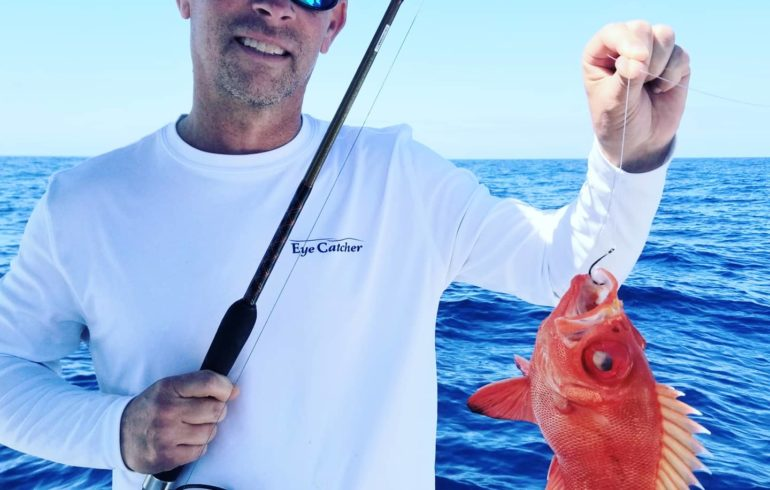 man holding fish from deep sea fishing
