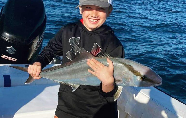 kid holding fish from deep sea fishing